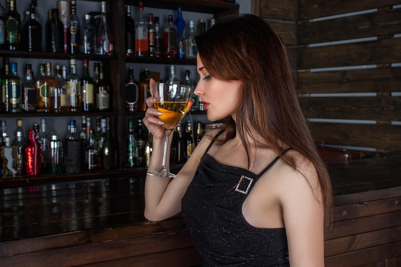 Mädchen trinkt Wein an der Bar