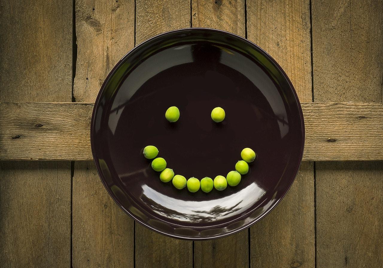 Teller mit Erbsen bilden ein frohes Gesicht